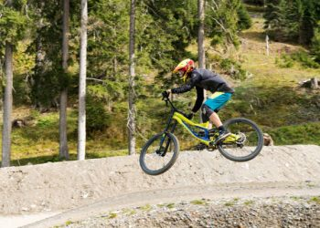 Lenzerheide, GR / Switzerland, - 12 October, 2019: downhill mountain biker jumping high and riding hard in Lenzerheide in the Swiss Alps