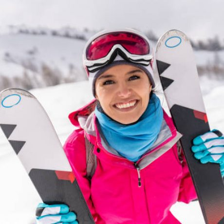 """Portrait of a happy Latin American woman skiing in the Alps and looking at the camera smiling -"""" winter sports concepts"""
