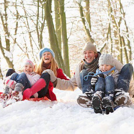 Family Having Fun Sledging Through Snowy Woodland