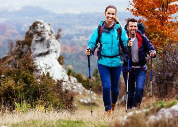 Fall. Couple Backpackers hiking on the path in mountains during autumn.